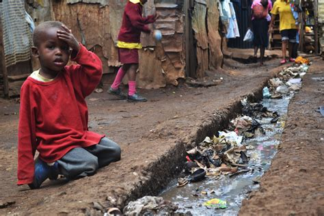 File:A young boy sits over an open sewer in the Kibera